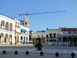 In the corner of the Plaza Vieja, a crane rises over the buildings.