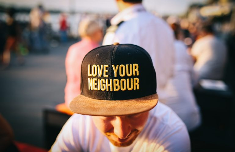 Group of people sitting, one with love your neighbor hat