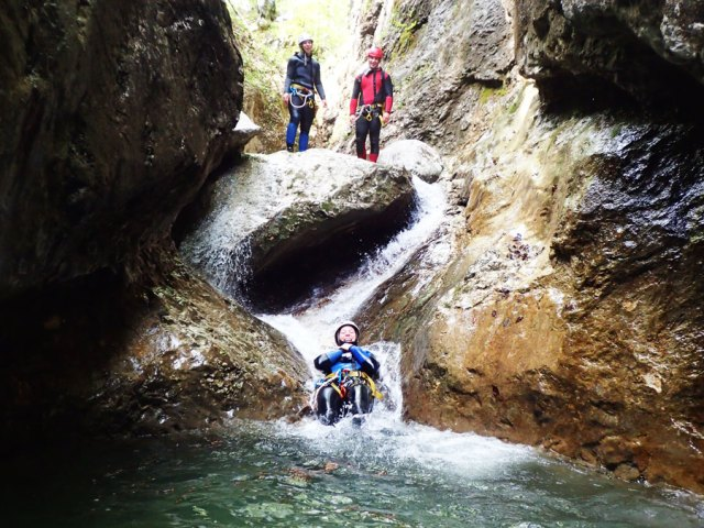 Canyoning guide looking at guest sliding down canyon riverbed near Bled Slovenia