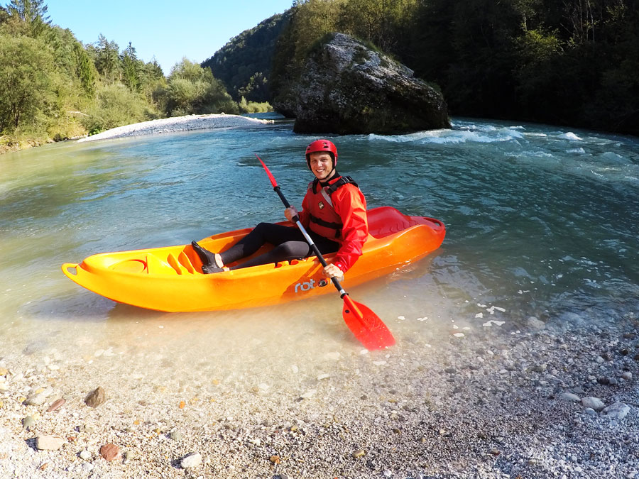 Person in orange sit on top kayak resting on shore of Sava river Bled Slovenia