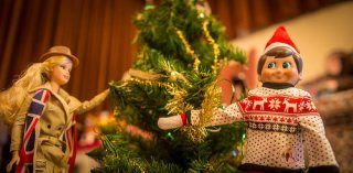 Elf on the Shelf trimming Christmas tree with Barbie