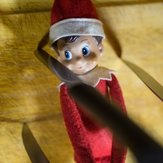 Elf on the Shelf watches a knife land close