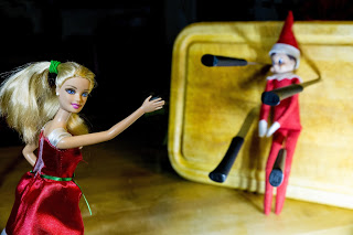 Elf on the Shelf helped out Barbie with her knife throwing act.