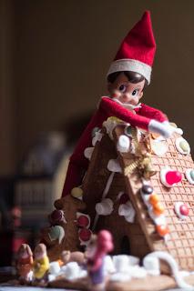 Giant Elf on the shelf terrorizing gingerbread house