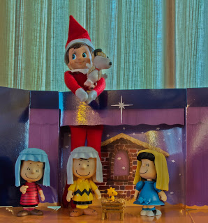 Elf on the shelf in Christmas nativity with Charlie Brown