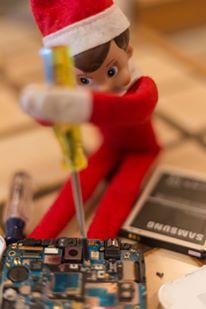 Elf on the shelf fixing a samsung phone
