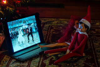 Elf on the shelf watches a movie with red head barbie