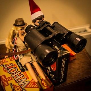Elf on the shelf looking through binoculars with Barbie