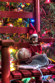 Elf on the shelf knitting a scarf in a red rocking chair