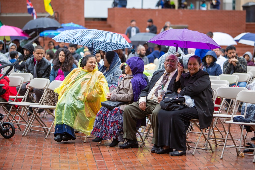 Happy crowd in the rain of Portland watching a live stream of a concert on an LED screen