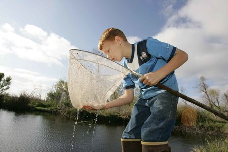 young angler looking into fishing net