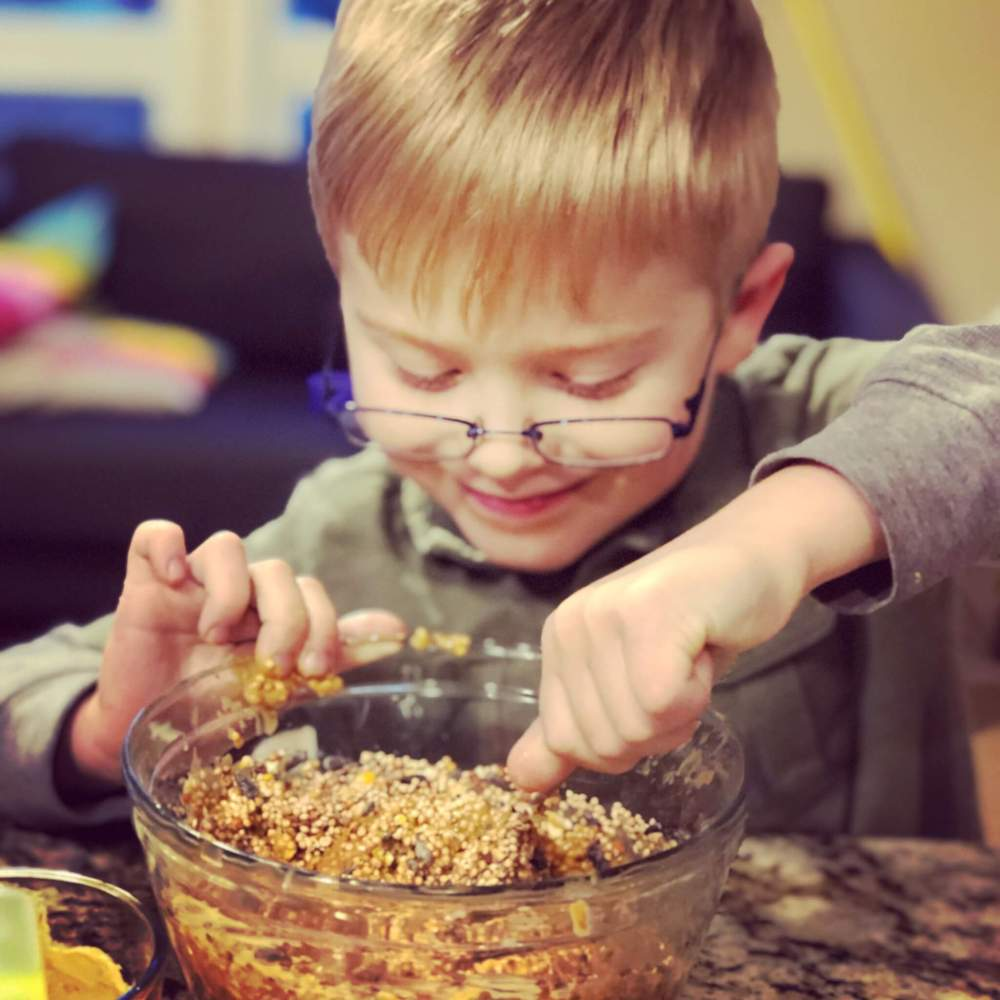 kid smiling while mixing bird seed and cashew butter in a glass bowl