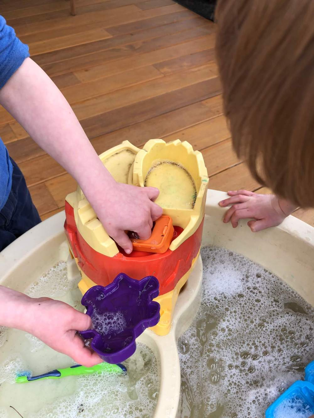 close up of children's hands as they play and clean up a water table full of soapy water and a toothbrush