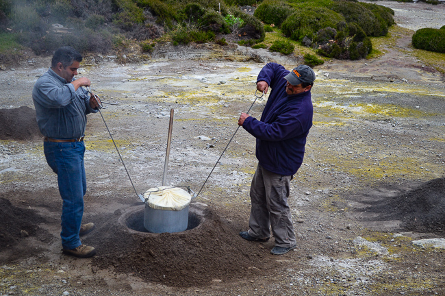 Men lowering pot for coizidos in Furnas, hot springs Azores