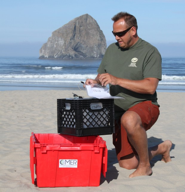 York Johnson, who works with the Tillamook Estuaries Partnership, collects a sample of coastal water in Pacific City, Ore. Ken Buesseler will analyze the sample for radiation from the Fukushima Daiichi nuclear power plant disaster. Photo courtesy of Woods Hole Oceanographic Institution (WHOI).