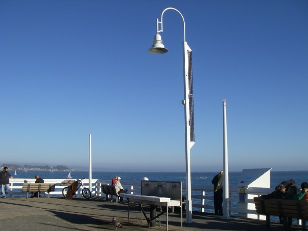 A new streetlight, powered by solar panels bolted to its spine, sits at the end of the Santa Cruz wharf.