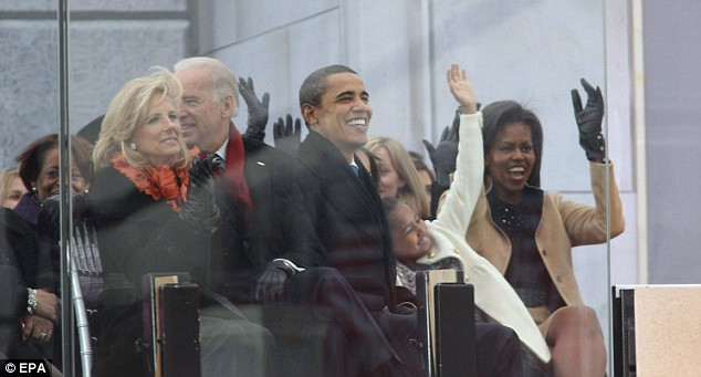 Barack Obama, wife Michelle and daughter Sasha - pictured with Vice President elect Joe Biden and wife Jill - wave to the crowd through bulletproof glass