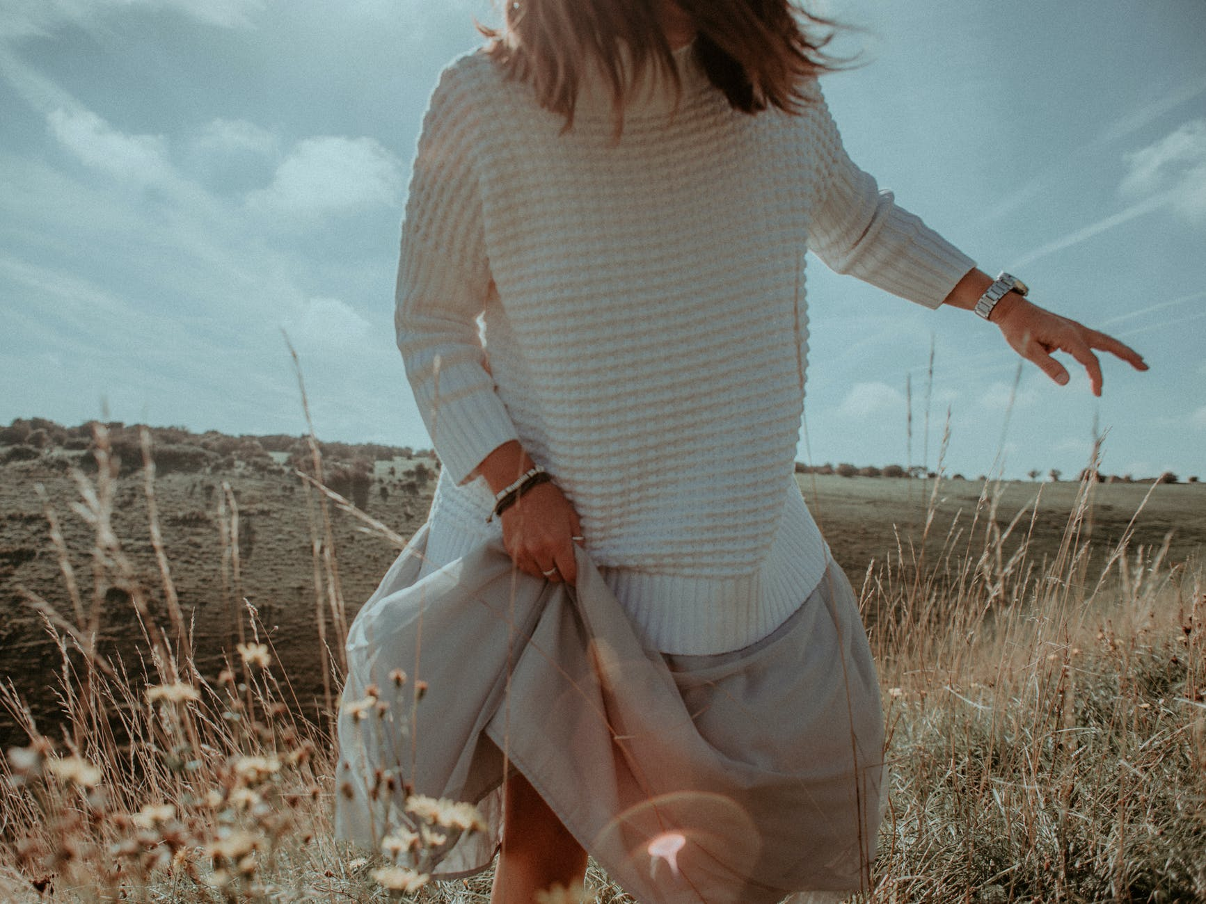 woman wearing white sweater and beige skirt