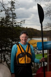 Man with a paddle in front of kayaks.
