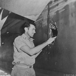 Louis Zamperini looks at hole in aircraft