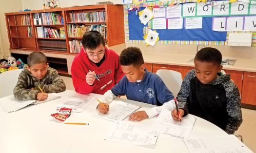 Photo by Shel Segal / OUTLOOK Maranatha High School sophomore Nathaniel Nguyen tutors Pasadena Rosebud Academy students (from left) Jacob Shorter, Jeremiah Turnbull and Manny Shorter as part of an outreach program at Maranatha.