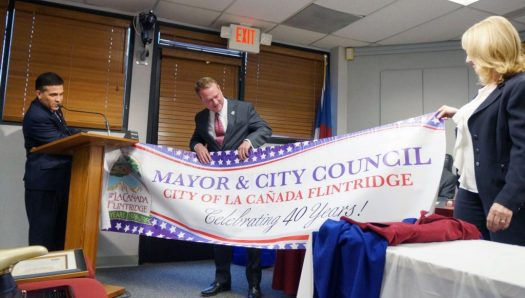 OUTLOOK photos City Manager Mark Alexander (left) and Ann Wilson unfurl the banner commemorating La Cañada Flintridge's 40th anniversary before giving it to outgoing Mayor Jonathan Curtis.
