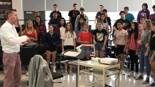 La Cañada High School choral director Jeff Brookey leads the audition vocal ensemble for grades 9-12 as it performs warmups for the voice.