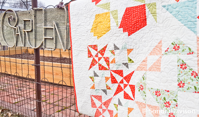 Bloom-Topia quilt draped on garden fence