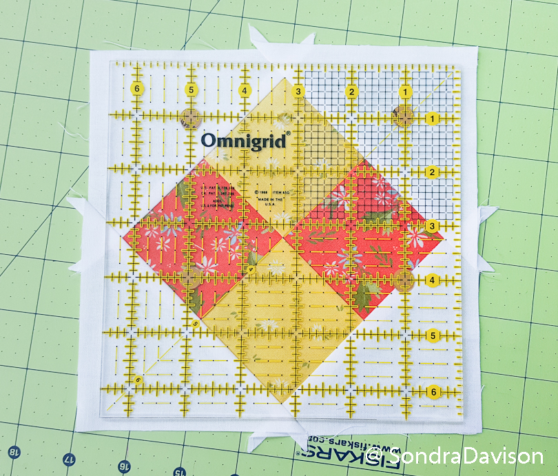aligning an omnigrid ruler on a quilt block