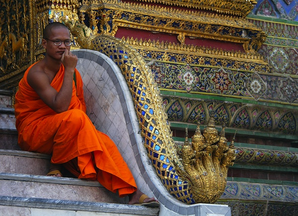 Buddhist monk resting in front of the Royal Palace in Bangkok, Thailand