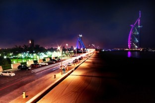 Dubai's iconic Burj Al Arab, illuminated by color-changing lights at night, is a sight to behold.