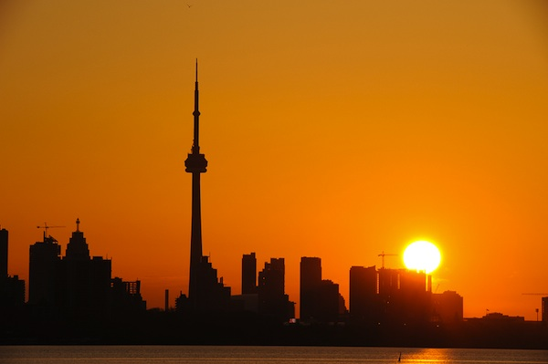 Modern building and CN Tower in downtown Toronto as silhouette