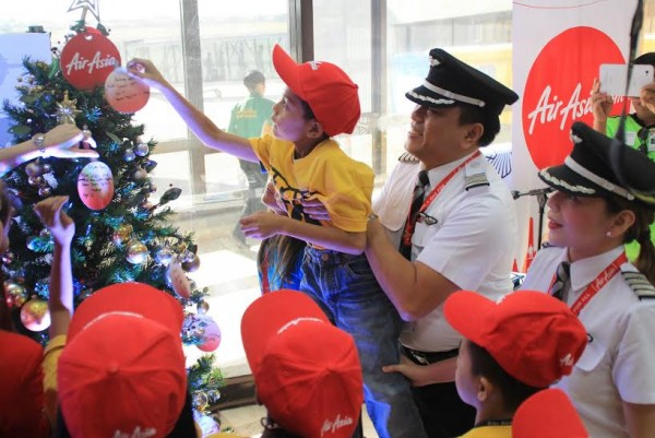 Captain Dexter Commendador helps a young boy place his message in a Christmas tree during the launching of AirAsia's newest flight from Cebu to Davao