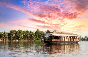House boat in backwaters near palms at dramatic sunset sky in Alappuzha Kerala India