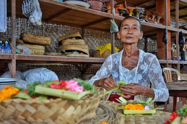 A Balinese Lady weaving small baskets to be used for offerings