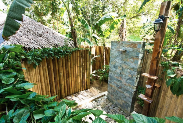 A one-of-a-kind shower experience among the greens, river rocks and bamboo sticks