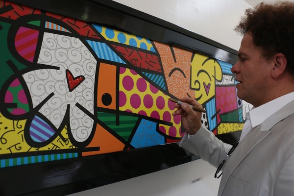 Visiting Brazilian pop artist Romero Britto autographs his work 'The Hug' during the Philexcel Art Center inauguration.