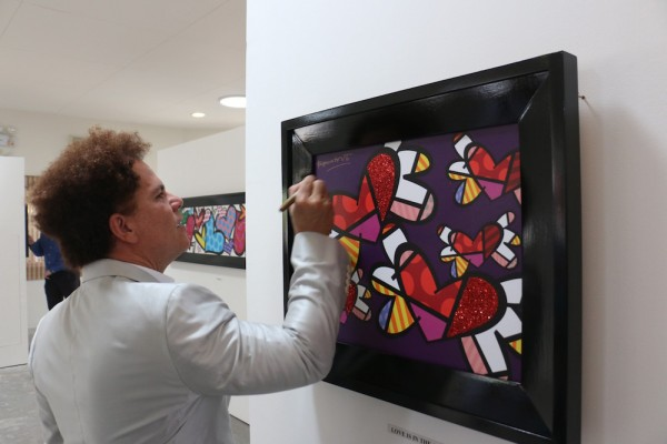 Visiting Brazilian pop artist Romero Britto autographs his work 'Love Is in the Air' during the Philexcel Art Center inauguration.