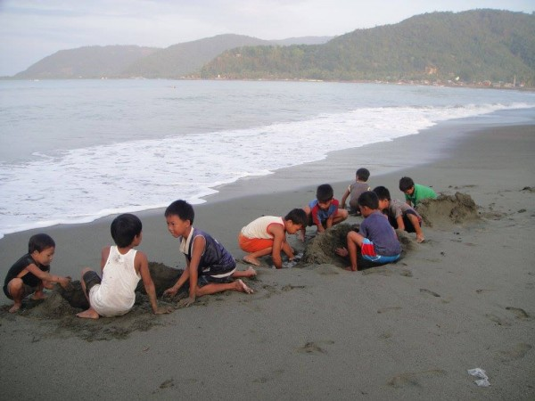 Baler kids playing on the sand at sundown