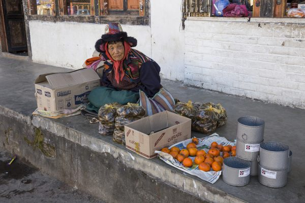 A Woman Sells Food On The Sidewalk Of The Main Street Of Paro.