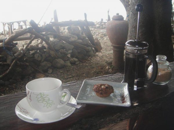 A solitary coffee break by the rocky shore