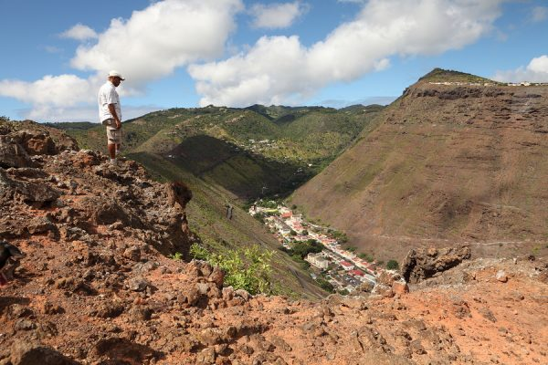 Walker stopping to admire the view from a trail on the hillside above Jamestown the capital of the Island of St Helena