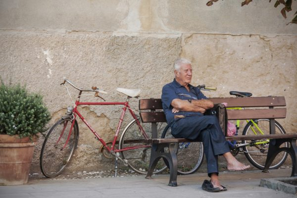 An old local sits on one of the numerous benches scattered around town watching the world go by.