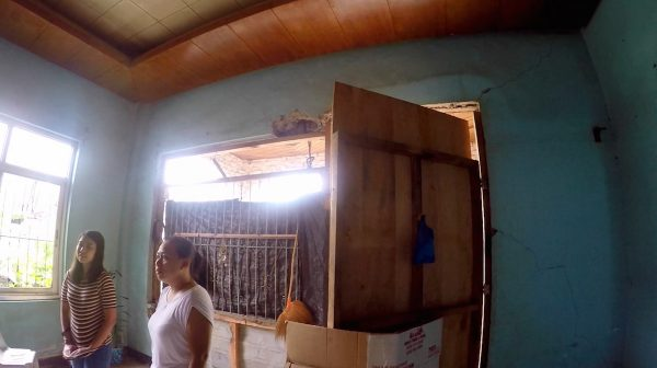 A makeshift cover of corrugated roof, wood and steel hide the pierced wall of the living room from the outside