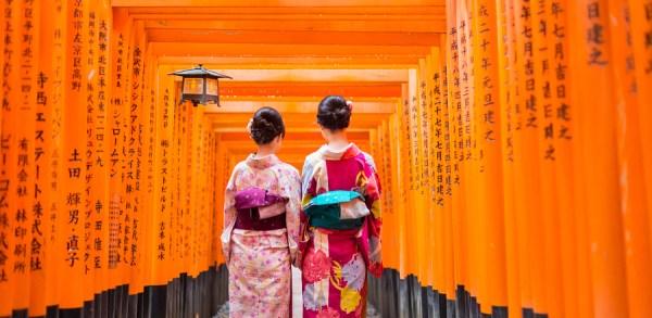Two local tourists wearing Kimono along red wooden Tori Gate at Fushimi Inari Shrine in Kyoto, Japan.