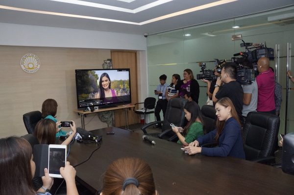 Tourism Secretary Wanda Teo (center) views Miss Universe Pia Wurtzbach's video message with some TV news representatives during an interview opportunity.