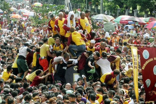 """Devotees need to swim and climb to the sea of people to touch or kiss the statue of the Black Nazarene on Monday (Jan. 9, 2017) during the """"Traslacion"""" at Liwasang Bonifacio former Plaza Lawton in Manila. (PNA photo by Oliver Marquez) lgi/fom"""