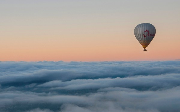 A balloon floats silently above a sea of white clouds.