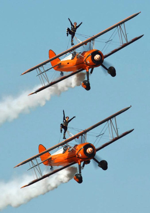 Fearless females doing stunts while strapped to Stearman aircraft in flight