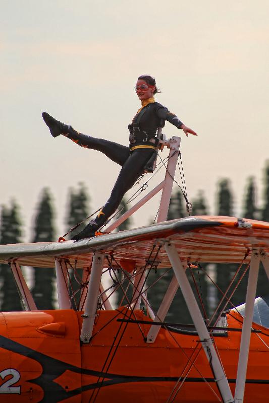 WingWalker Katie Hobbs performing graceful acrobatics movements under pressure and over the plane